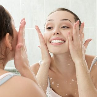 34010405 - young woman washing her face with clean water in bathroom