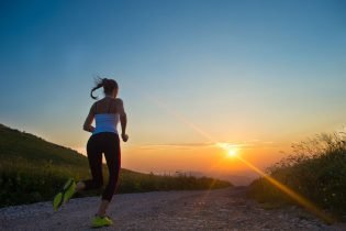32308535 - woman running outdoor on a mountain road at summer sunset