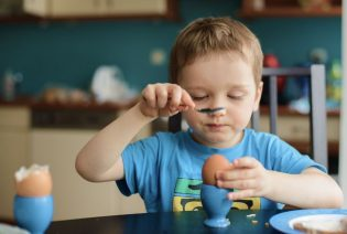 19225360 - small happy three year old boy breaks the egg on breakfast