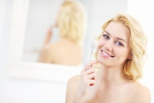 40164198 - a picture of a young woman using face cleansing brush in the bathroom