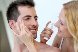 16949341 - woman applying sunscreen on her boyfriend's cheeks