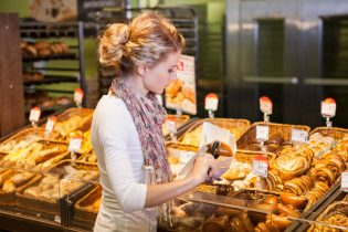 63730011 - young woman buying fresh bread in bakery