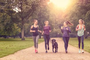 45120351 - four healthy young women jogging at the park in the afternoon with a pet dog.