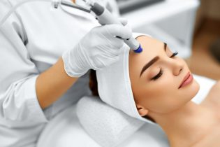 48892712 - face skin care. close-up of woman getting facial hydro microdermabrasion peeling treatment at cosmetic beauty spa clinic. hydra vacuum cleaner. exfoliation, rejuvenation and hydratation. cosmetology.