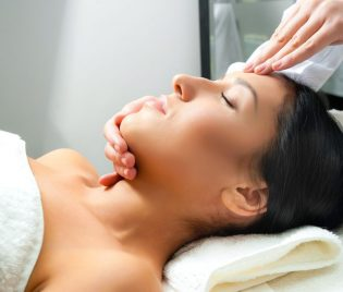 11354453 - beautiful young woman receiving facial massage with closed eyes in a spa center