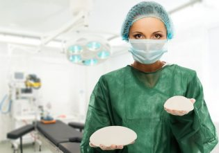 26674565 - plastic surgeon woman holding different size silicon breast implants in surgery room interior