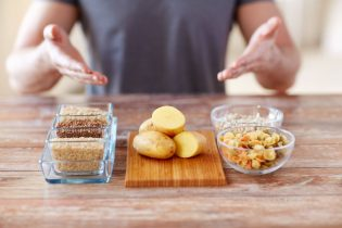 53927719 - healthy eating, diet and people concept - close up of male hands showing carbohydrate food on table