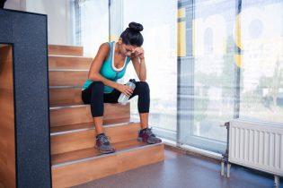 44255763 - tired woman sitting on the stairs with bottle of water in gym