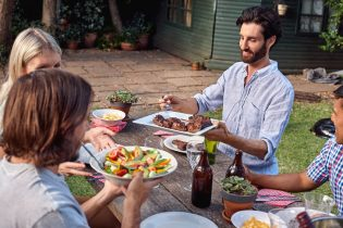 38626328 - group of friends having outdoor garden barbecue salad dinner with drinks