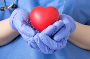 39266426 - female doctor holding a red heart shape