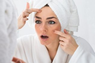 39435265 - close-up of worried woman looking at pimple on face in mirror