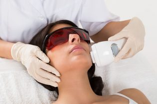 39657487 - close-up of beautician giving epilation laser treatment on woman's face