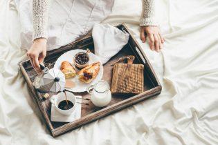 44171876 - woman having breakfast in bed. window light