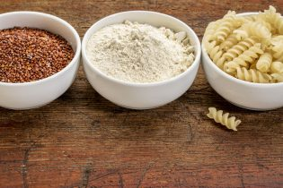 39219042 - gluten free quinoa grain, flour and pasta - three small ceramic bowls against rustic wood with a copy space
