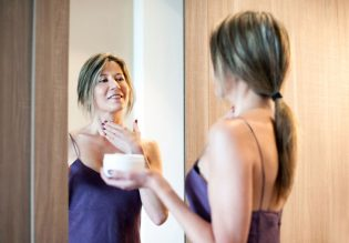 60377090 - cheerful beautiful woman with long hair and purple night gown looking in mirror while applying wrinkle cream