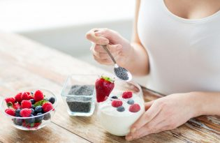 53497204 - healthy eating, vegetarian food, diet and people concept - close up of woman hands with yogurt, berries and poppy or chia seeds on spoon