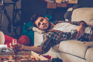 54359999 - young handsome man holding pizza slice and beer can while lying on sofa in messy room after party