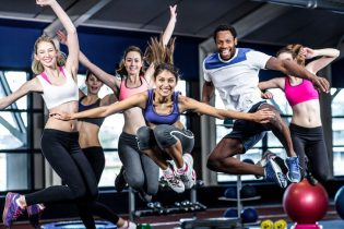 50632898 - fit group smiling and jumping in gym