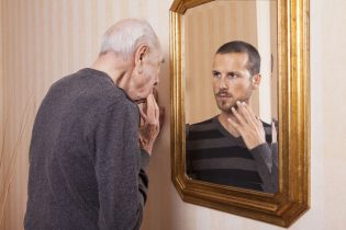34882267 - young man looking at an older himself in the mirror