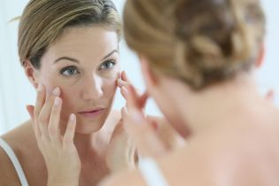 34768682 - middle-aged woman applying anti-aging cream