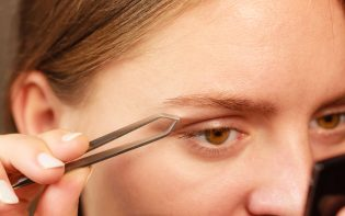 51782951 - woman plucking eyebrows depilating with tweezers closeup part of face. girl tweezing eyebrows.