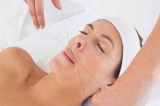 30914745 - close up of a hands threading beautiful woman's upper lip