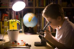 55891631 - close-up portrait of young student working with microscope in his room. child and science experiments. kid studying samples under the microscope. preparing for science lesson.