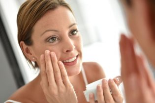 50065580 - woman applying facial cream on her face