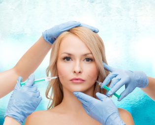 27759647 - beauty and cosmetic surgery concept - woman face and beautician hands with syringes
