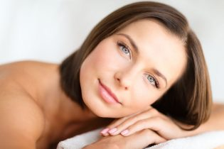 53974491 - health, beauty, resort and relaxation concept - beautiful woman in spa salon lying on the massage desk